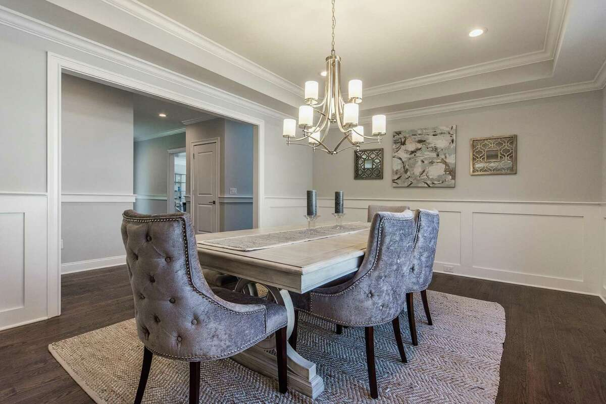 The formal dining room of this new colonial house at 48 Clinton Avenue has a tray ceiling and wainscoting on the lower walls.