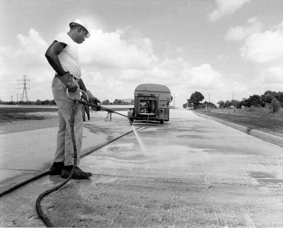In 1970, a worker steam-cleans a frontage road on the long-awaited Northwest Freeway between Mangum and Pinemont. The Texas Highway Department expects the roads to be open in about three weeks. Right-of-way preparation for the next stretch of frontage roads, Pinemont ot Jersey Village, is about 75 per cent complete. The freeway will ultimately link Houston and Hempstead, following U.S. 290 in places. Photo: Jerry Click/Houston Chronicle