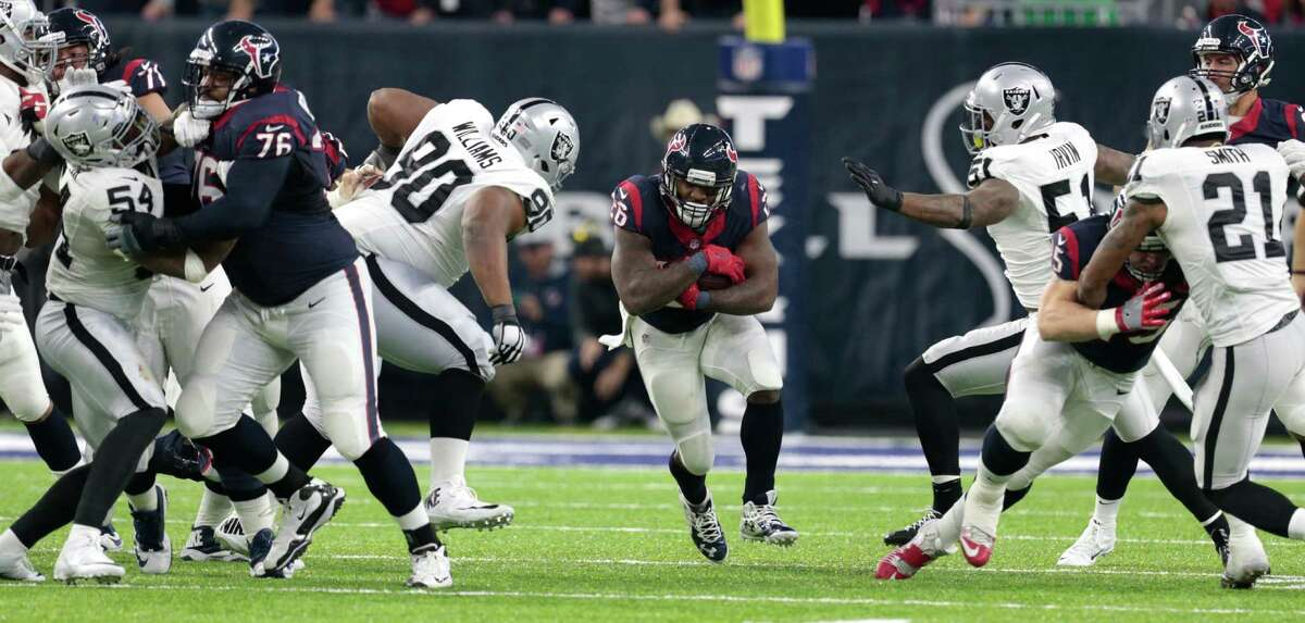 Houston Texans running back Lamar Miller (26) runs through a hole in the Oakland Raiders defensive line during the third quarter of an AFC Wild Card Playoff game at NRG Stadium on Saturday, Jan. 7, 2017, in Houston. ( Brett Coomer / Houston Chronicle )