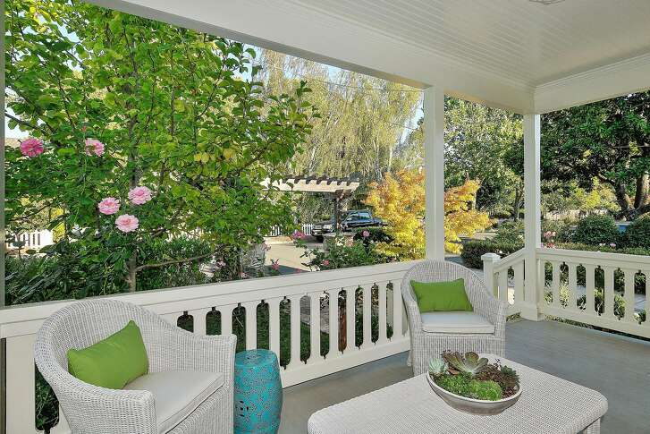 A covered porch overlooks the front yard.