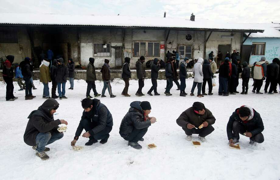 Five migrants squat in the snow as they eat a warm meal distributed by aid groups as others queue for their portion outside a crumbling warehouse that has served as a makeshift shelter in Belgrade, Serbia, Thursday, Jan. 12, 2017. Migrants have been exposed to freezing temperatures and snow as extreme winter weather gripped Serbia and other parts of Europe last week. Photo: Darko Vojinovic, AP / Copyright 2017 The Associated Press. All rights reserved.
