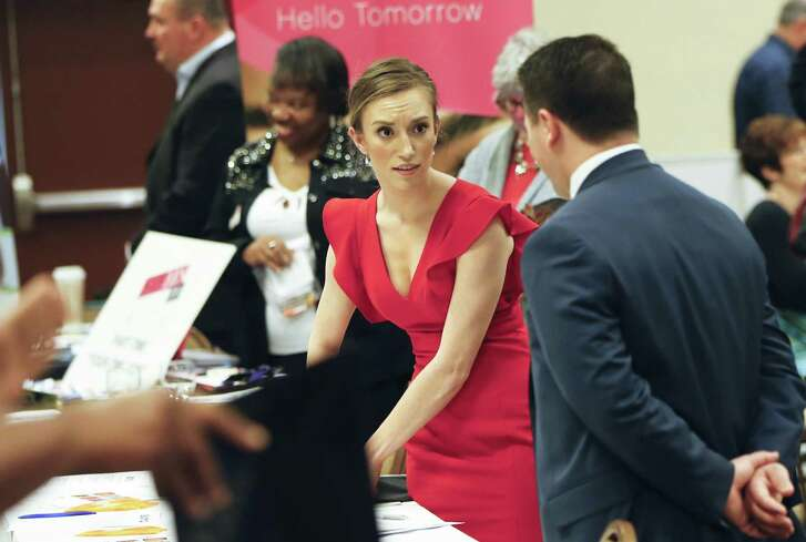 Job recruiters work their booths at a job fair in Pittsburgh. Weekly applications for unemployment aid rose 10,000 to a seasonally adjusted 247,000, the Labor Department said Thursday. The increase in applications comes a week after they fell to nearly a 43-year low. Applications have been below 300,000 for 97 straight weeks, the longest such streak since 1970.