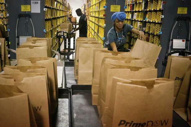 FILE - In this Wednesday Dec. 21, 2016, file photo, Miracle Stewart, right, an employee of Amazon PrimeNow, prepares bags to fill with orders from customers making purchases, at a distribution hub in New York. Amazon said Thursday, Jan. 12, 2017, that it plans to hire 100,000 people across the U.S. over the next 18 months. The online retailer says they are full-time jobs that come with benefits. Many of the jobs will be at new fulfillment centers being built in several states, including California, Florida and Texas. (AP Photo/Bebeto Matthews, File)