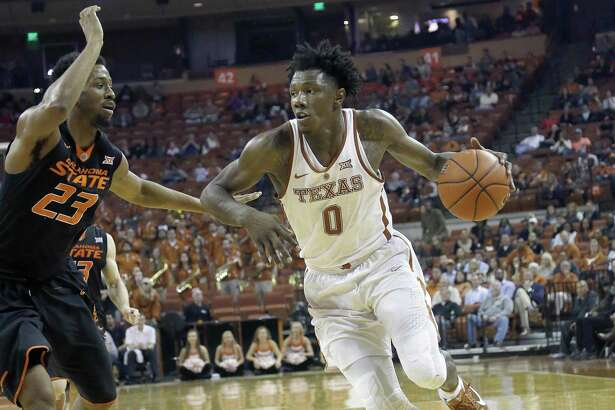 Tevin Mack of the Texas Longhorns drives around Leyton Hammonds of the Oklahoma State Cowboys at the Erwin Center on Jan/ 4, 2017 in Austin.