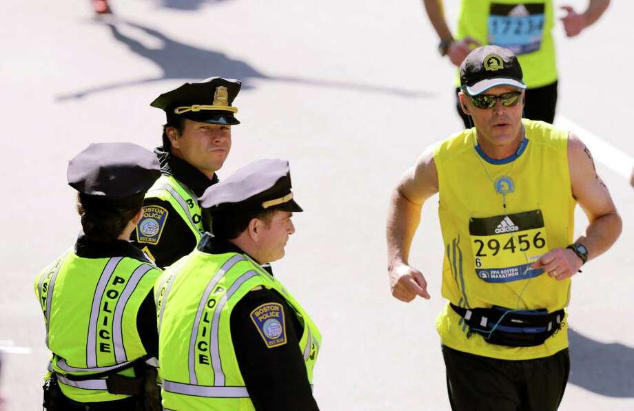 "FILE - In this April 18, 2016 file photo, actor Mark Wahlberg, center left, dressed as a Boston Police officer, watches runners cross the finish line as he films a scene for the ""Patriot's Day"" movie at the 120th Boston Marathon in Boston. Wahlberg's movie about the bombings during the 2013 Boston Marathon premiers in limited release on Wednesday, Dec. 21, in Boston, New York and Los Angeles, before a nationwide release on Jan. 13, 2017. (AP Photo/Charles Krupa, File) ORG XMIT: BX601 Photo: Charles Krupa / FILE"