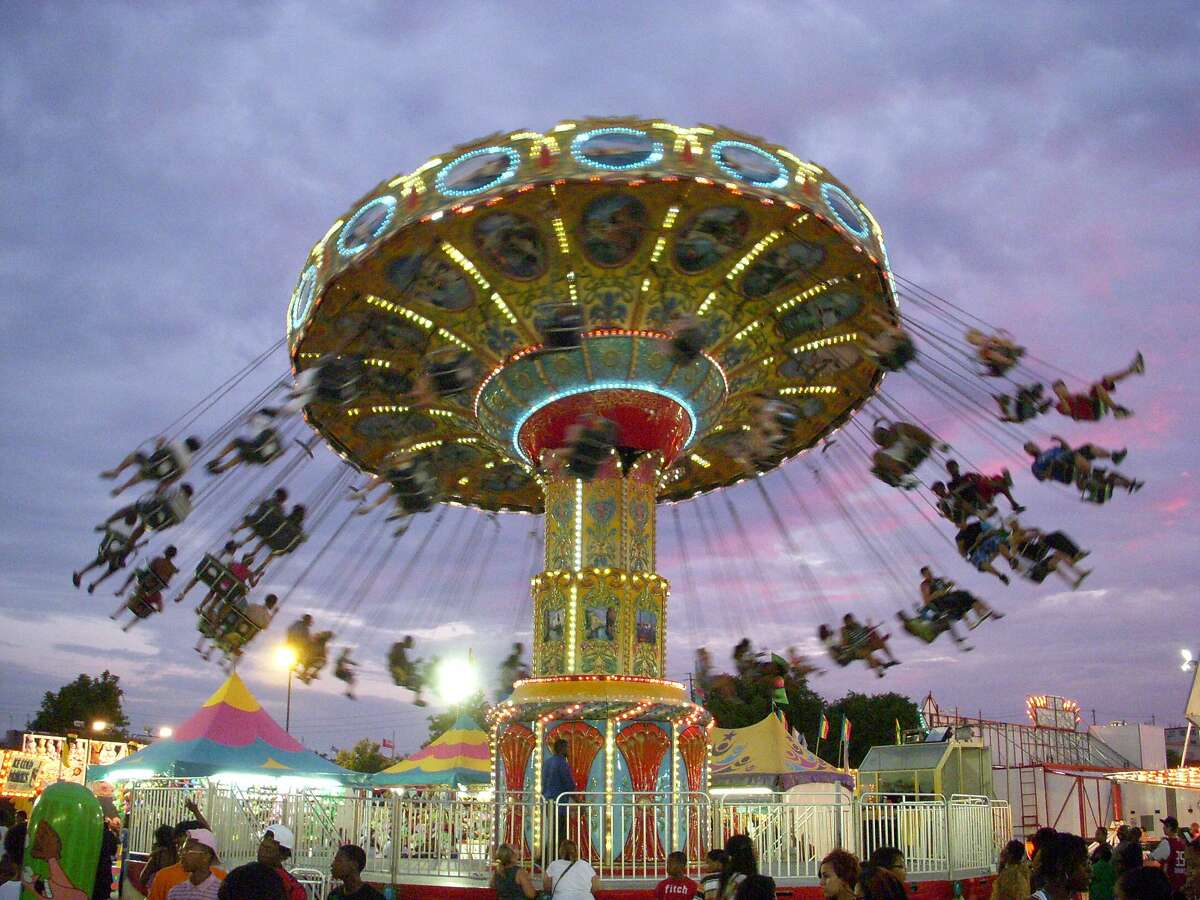 Fans swirl around on the Wave Swinger ride at the rodeo's carnival.