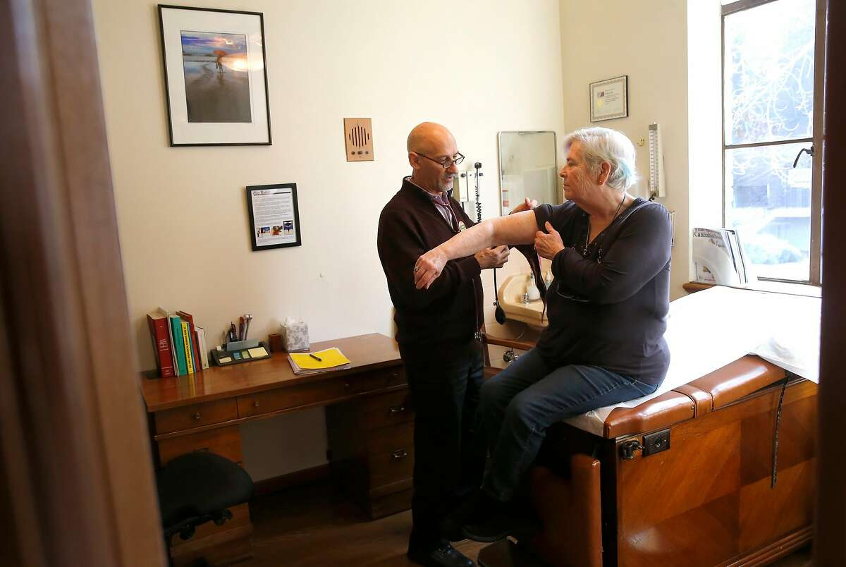 Dr. Frank Lucido meets with his patient Carla Newbre of Oakland in his office on Thursday Jan. 12, 2017, in Berkeley, Ca. Newbre was prescribed medical Cannabis by Dr. Lucido for her muscle spasms and pain.