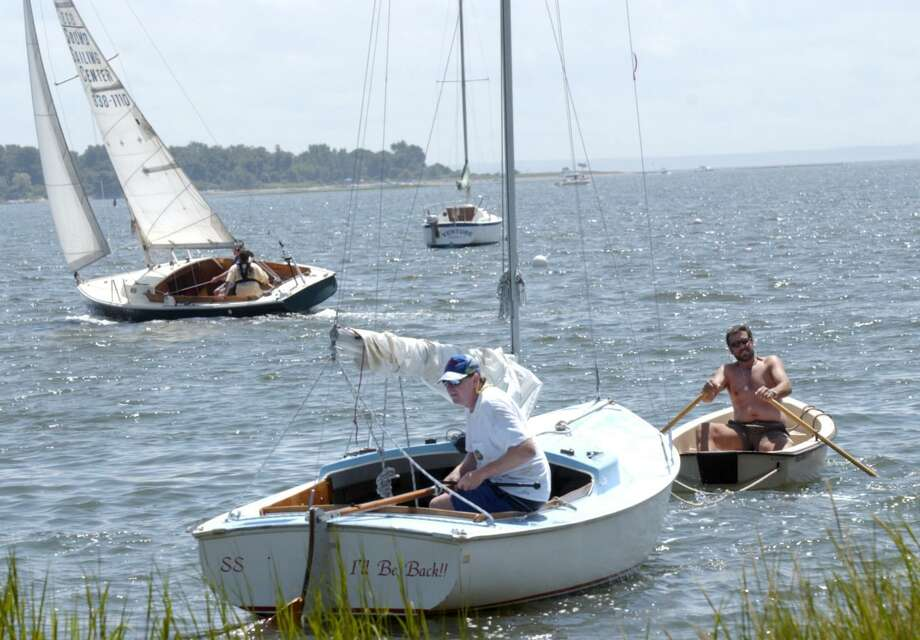 Norwalk_073104_ Harborview community in South Norwalk. Tom Brown tows via rowboat, Robert Taylor in a Rhodes 19 sailboat. The two had just finished working on the boat on shore, and were taking it back to its mooring. Mark Conrad/Staff Photo Harbor View Photo: ST