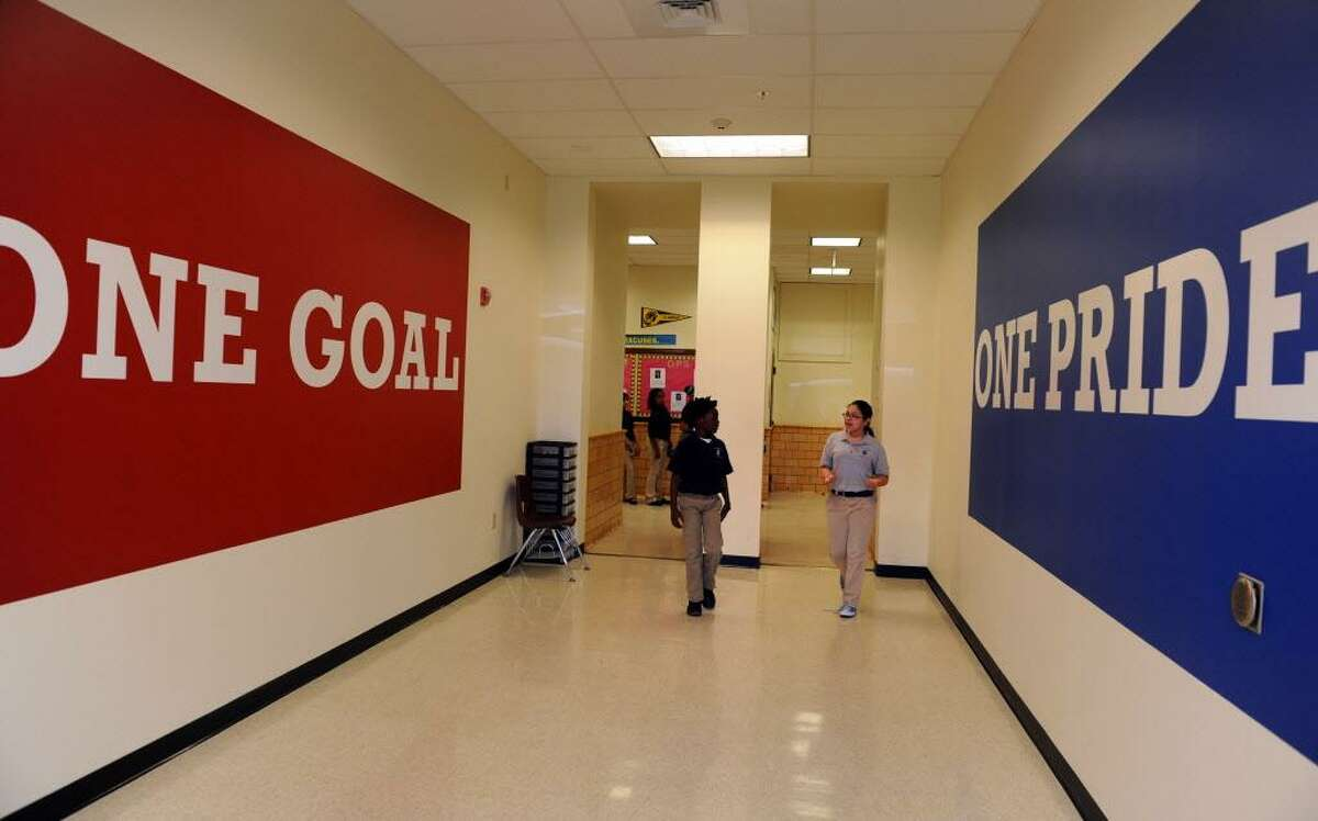 Fifth grade student Anthony Montgomery and eighth grade student Anabell Pichardo walk through the halls of the newly renovated Achievement First Bridgeport Academy Middle School in Bridgeport Thursday, May 31, 2012.