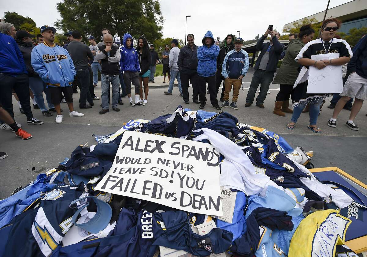 Fans stand around a pile of Chargers memorabilia in front of San Diego Chargers headquarters after the team announced that it will move to Los Angeles Thursday Jan. 12, 2017, in San Diego. (AP Photo/Denis Poroy)