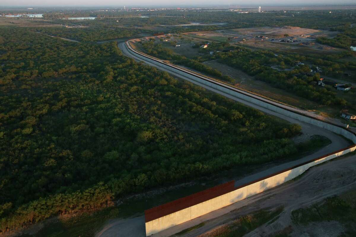 As the sun rises, the U.S.-Mexico border wall is revealed across a span of Hidalgo County near McAllen. The wall cuts through farmland and some residential areas along its route through the South Texas border.