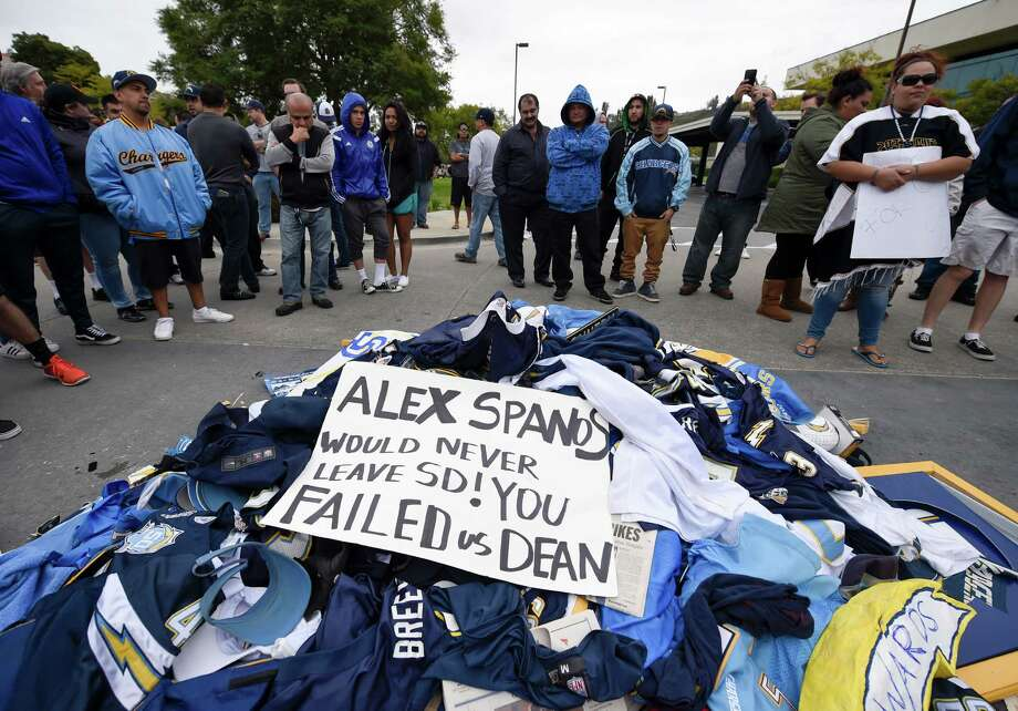 Fans stand around a pile of Chargers memorabilia in front of San Diego Chargers headquarters after the team announced that it will move to Los Angeles Thursday Jan. 12, 2017, in San Diego. (AP Photo/Denis Poroy) ORG XMIT: CADP116 Photo: Denis Poroy / FR59680 AP