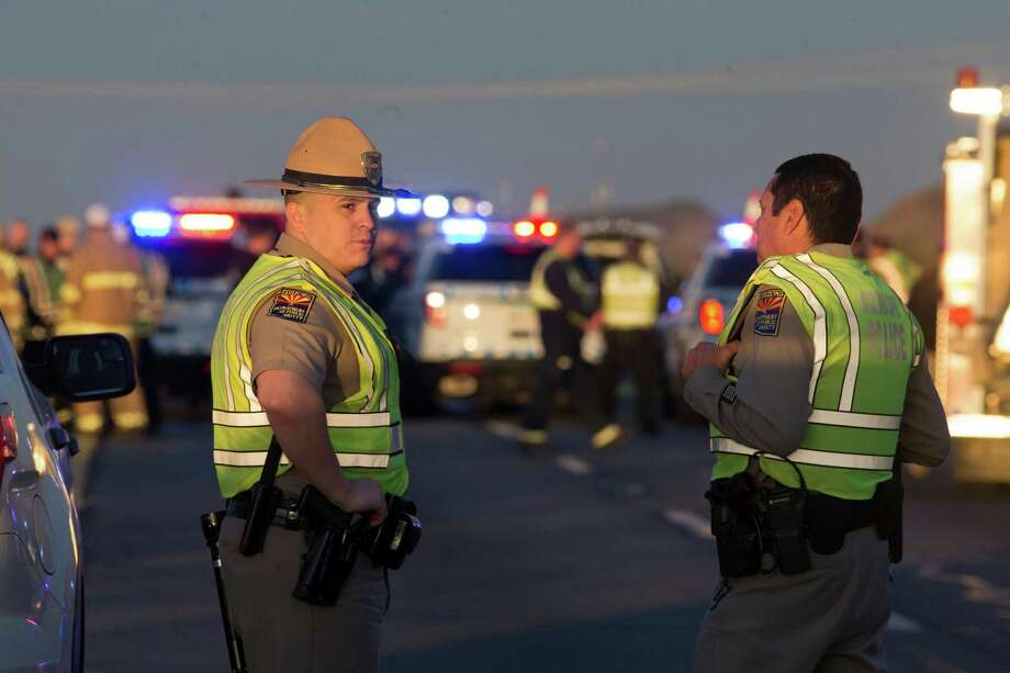 Emergency personnel gather at the scene where an Arizona Department of Public Safety trooper was shot, Thursday, Jan. 12, 2017, at the scene of a rollover accident on Interstate 10 near Tonopah, Ariz. An Arizona state trooper stopped to help at a car wreck along the remote highway Thursday when he was shot and wounded in an ambush by a man who was bashing the officer's head against the pavement until a passing driver shot him to death, authorities said.   The trooper suffered a severe wound to his shoulder and upper chest but he is expected to recover at a hospital. (Mark Henle/The Arizona Republic via AP) Photo: Mark Henle, MBO / The Arizona Republic