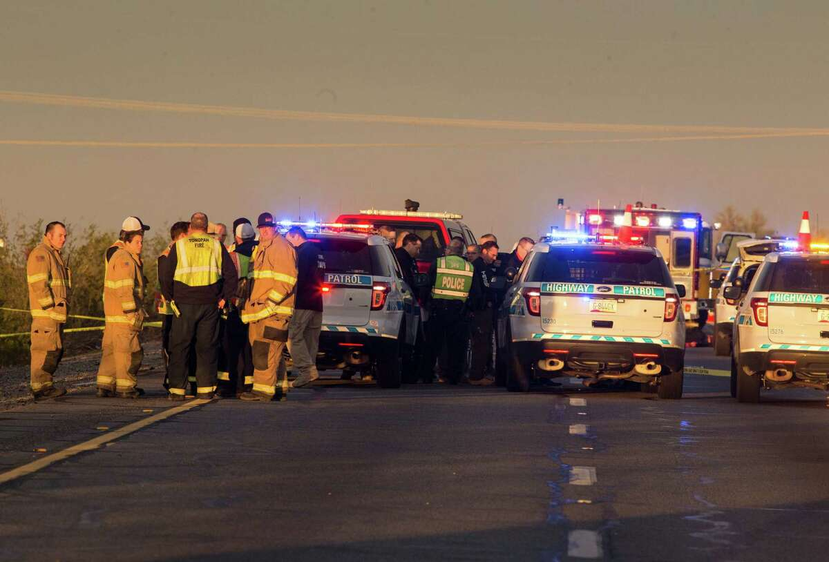 Emergency personnel gather at the scene where an Arizona Department of Public Safety trooper was shot, Thursday, Jan. 12, 2017, at the scene of a rollover accident on Interstate 10 near Tonopah, Ariz. An Arizona state trooper stopped to help at a car wreck along the remote highway Thursday when he was shot and wounded in an ambush by a man who was bashing the officer's head against the pavement until a passing driver shot him to death, authorities said. The trooper suffered a severe wound to his shoulder and upper chest but he is expected to recover at a hospital. (Mark Henle/The Arizona Republic via AP)