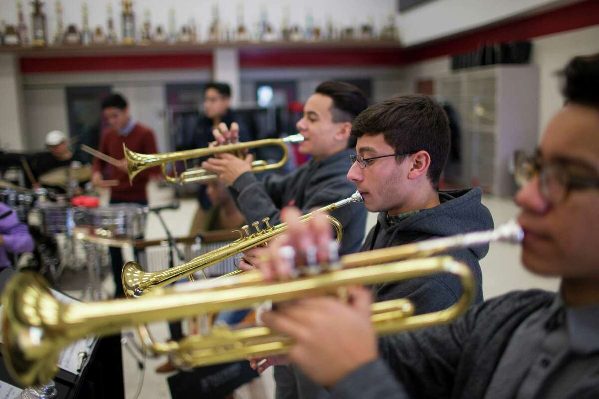 Andrew Camey, 16, Angel Tirado, 17, and Joseph Jenzen, 14, play trumpets as part of Caliente.