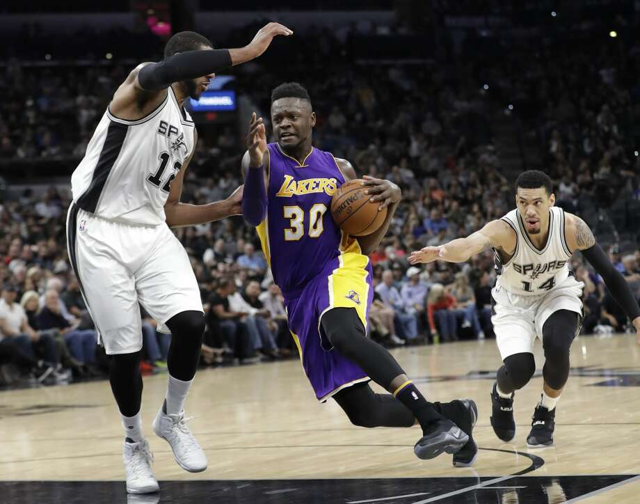Los Angeles Lakers forward Julius Randle (30) drives between San Antonio Spurs forward LaMarcus Aldridge (12) and guard Danny Green (14) during the first half of an NBA basketball game, Thursday, Jan. 12, 2017, in San Antonio. (AP Photo/Eric Gay) Photo: Eric Gay/Associated Press