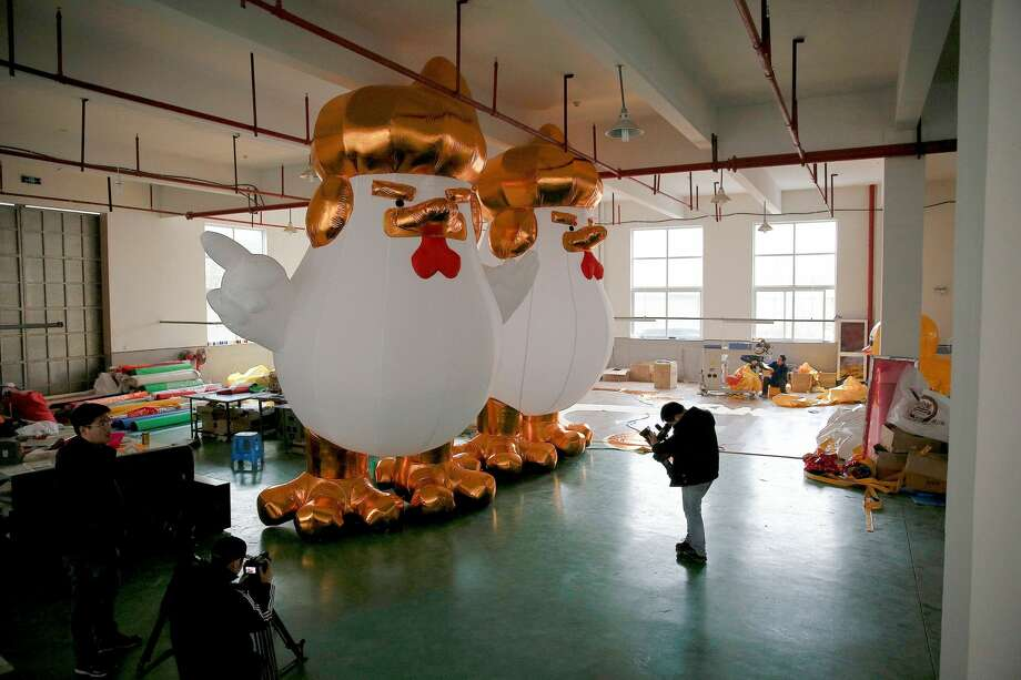 A cameraman films an inflatable chicken that local media say bears resemblance to U.S. President-elect Donald Trump as a Chinese factory braces for the Year of the Rooster in Jiaxing, Zhejiang province, China, Jan. 12, 2017. Photo: ALY SONG/REUTERS