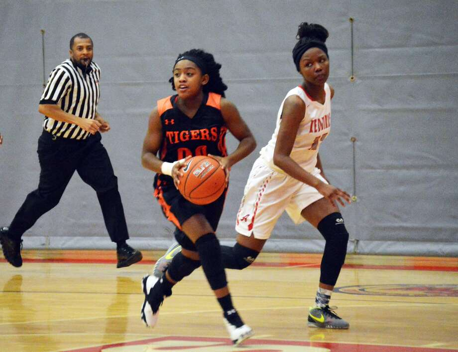 Edwardsville guard Quierra Love, left, prepares to pass the ball to a teammate during a fast-break opportunity against Alton in the second quarter.