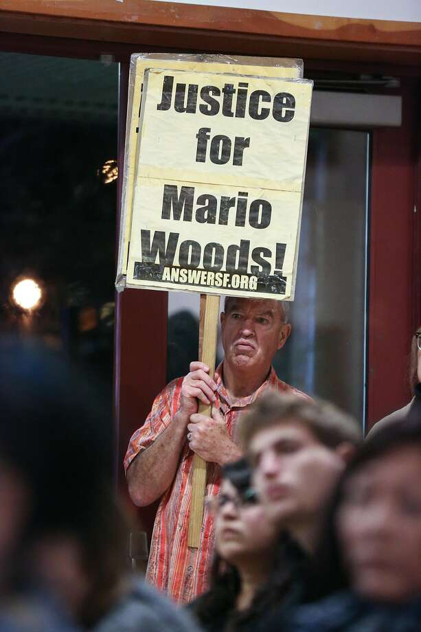 A man holds a sign in support of Mario Woods at the town hall meeting on January 12, 2017 to update the public about an officer involved shooting of an unarmed man that occurred on January 6th on the 500 block of Capitol Avenue in San Francisco, Calif. Photo: Amy Osborne, Special To The Chronicle