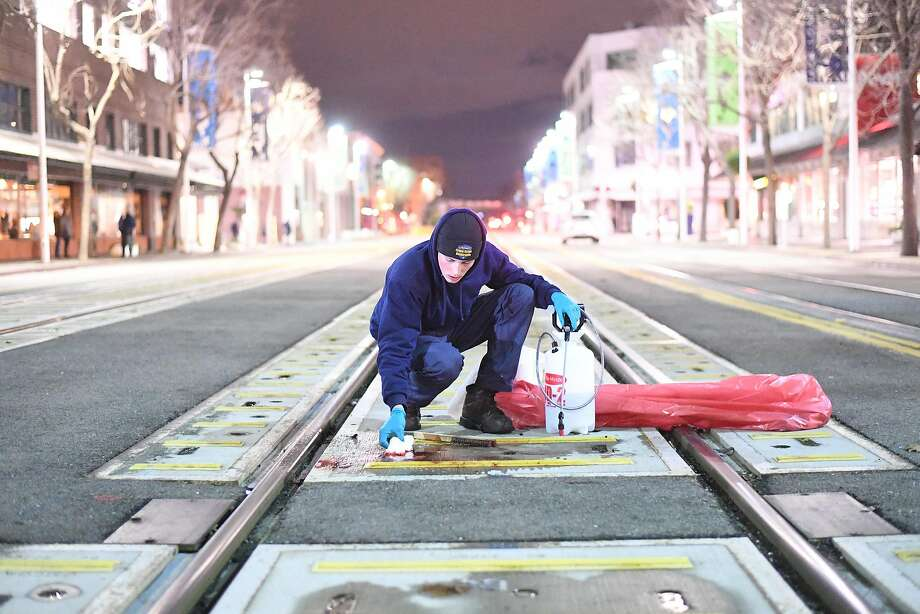 Brandon Scura of Advance Crime Scene Restoration cleans blood from railroad tracks in front of Yoshi's Jazz Club in Oakland, Calif., on Thursday, Jan. 12, 2017. Photo: Noah Berger, Special To The Chronicle