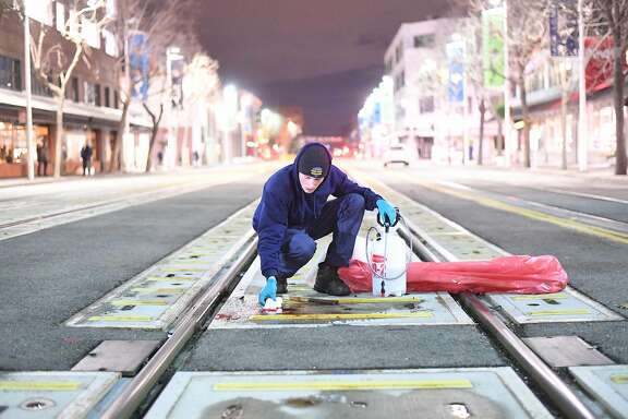 Brandon Scura of Advance Crime Scene Restoration cleans blood from railroad tracks in front of Yoshi's Jazz Club in Oakland, Calif., on Thursday, Jan. 12, 2017.