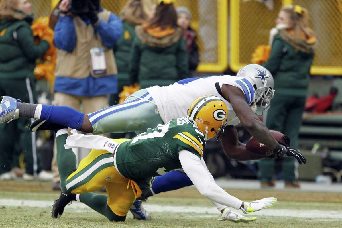 Dallas Cowboys wide receiver Dez Bryant (top) grabs a pass against Green Bay Packers cornerback Sam Shields during the second half of an NFC divisional playoff game on Jan. 11, 2015, in Green Bay, Wis. Bryant still gets stopped all the time by people who are sure the refs blew the replay on the Dallas receivers famous catch that wasn't.