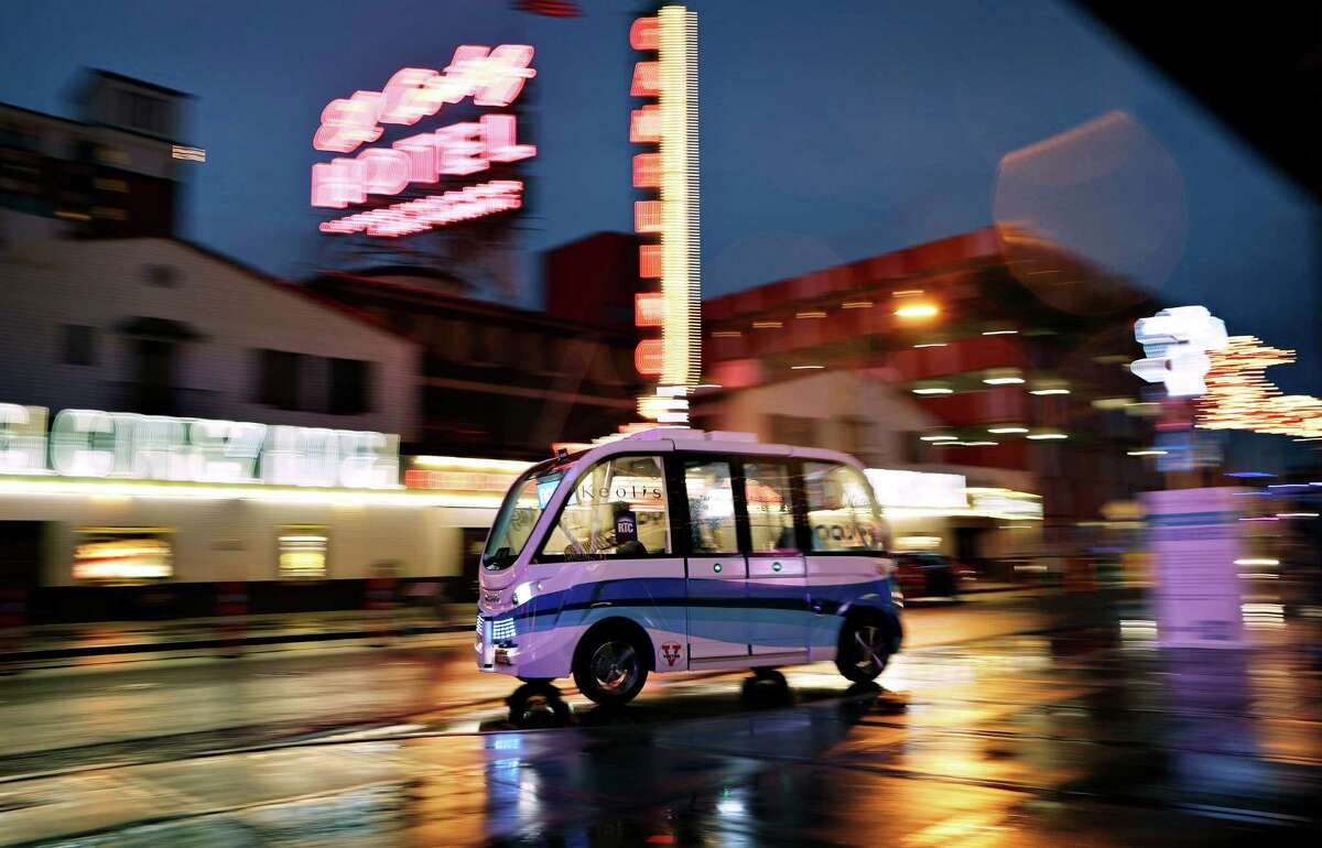 A Navya Arma autonomous vehicle drives down a street in Las Vegas on Jan. 12. The driverless electric shuttle has begun carrying passengers in a test program in a downtown Las Vegas entertainment district.