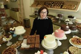 Owner Helene Godin poses behind the counter at By the Way Bakery in Greenwich, Conn. Wednesday, Dec. 21, 2016. Located at 19 E. Putnam Ave., the bakery opened Wednesday and serves a variety of pastries, cakes and other baked goods, as well as Stumptown coffee from Portland, Ore.