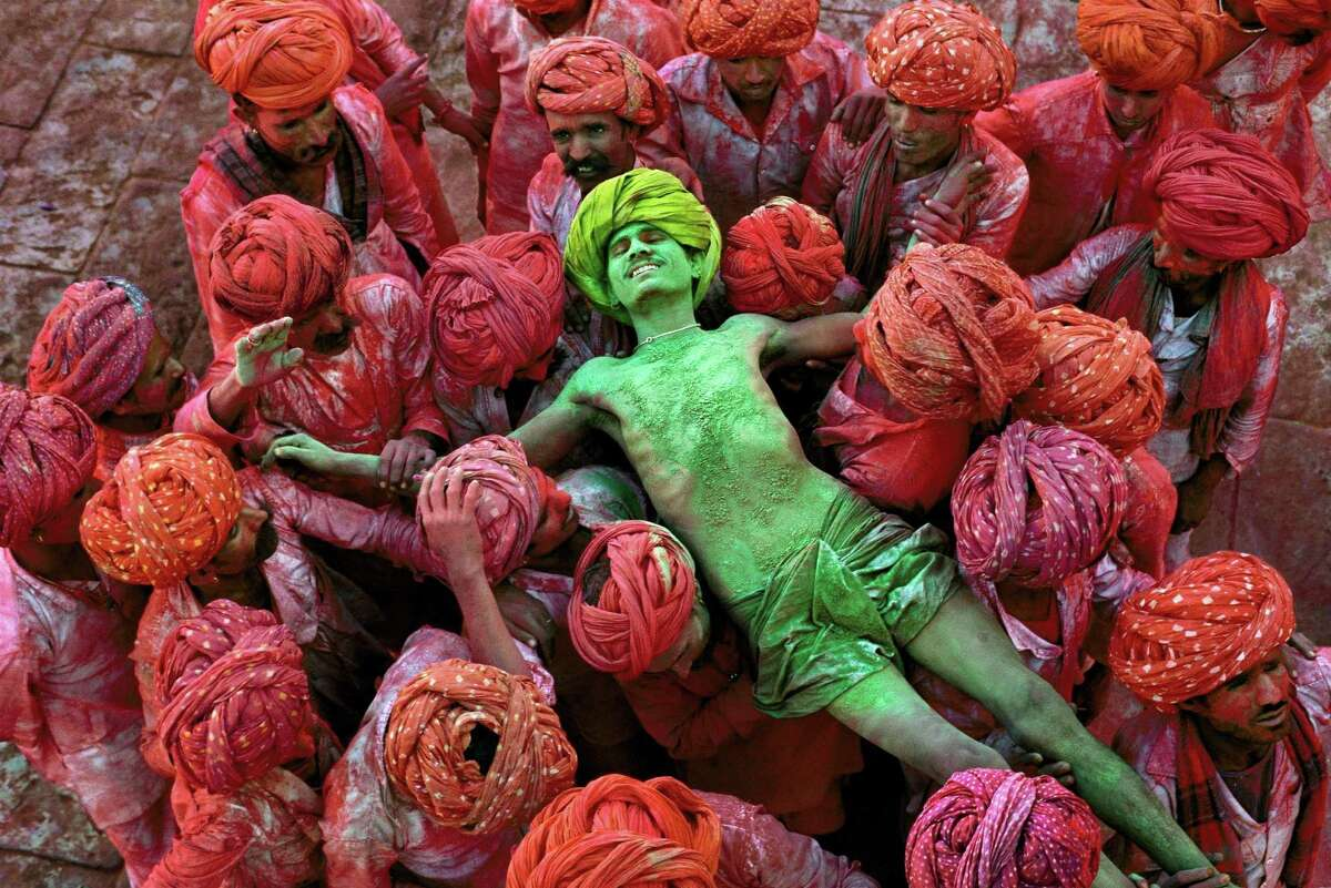 """""""Rajathan/1996"""" captures a crowd carrying a man during the Holi festival."""