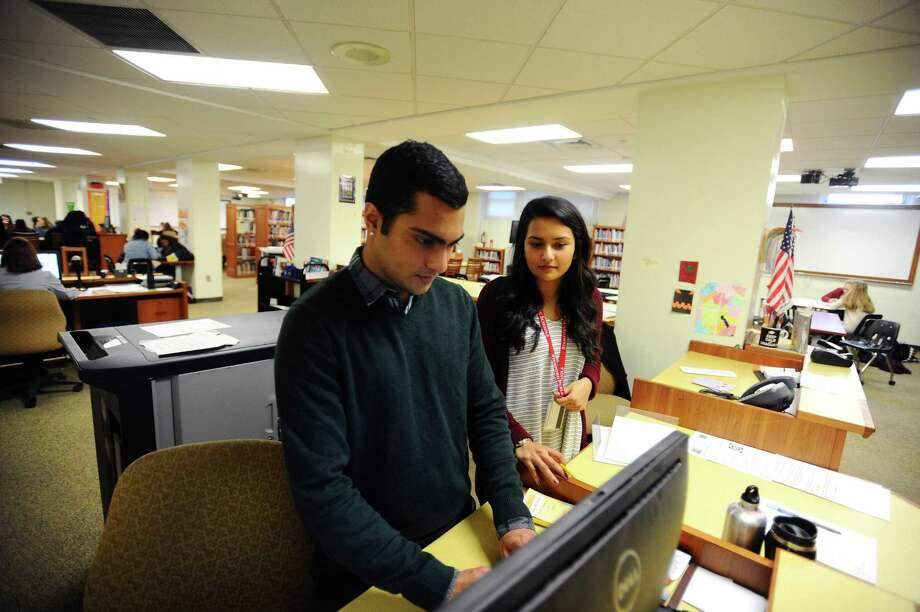 UConn Stamford students Nathan Nandagopal (left), 21, and Salaha Kabir, 25, work in the Stamford High School library as part of a new program aimed at giving college students work experience during their winter break in Stamford. Photo: Michael Cummo / Hearst Connecticut Media / Stamford Advocate