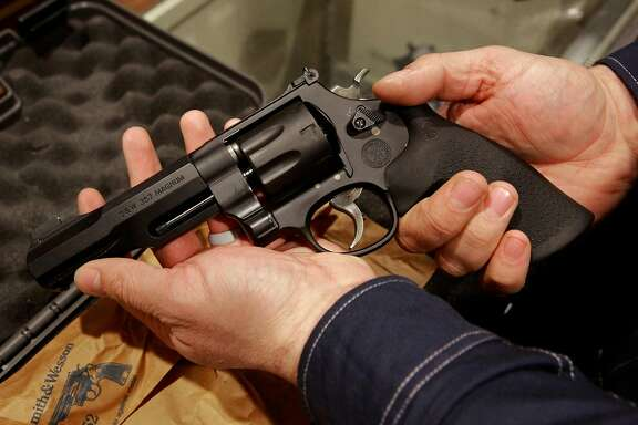 A customer displays the hand giuun he had purchased from Todd Settergren of Setterarms gun shop, on Friday Jan. 13, 2017, in Walnut Creek, Ca. Gun shop owner, Settergren says California gun laws have gone too far and he welcomes the chance that the federal government under the Trump administration will ease restrictions on concealed carry permits and specific weapon bans.