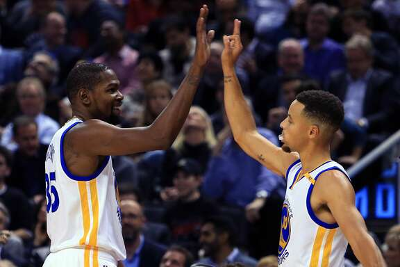 TORONTO, ON - NOVEMBER 16:  Kevin Durant #35 and Steph Curry #30 of the Golden State Warriors high five during the first half of an NBA game against the Toronto Raptors at Air Canada Centre on November 16, 2016 in Toronto, Canada.  NOTE TO USER: User expressly acknowledges and agrees that, by downloading and or using this photograph, User is consenting to the terms and conditions of the Getty Images License Agreement.  (Photo by Vaughn Ridley/Getty Images)