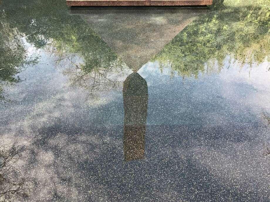 "A reflection of Barnett Newman's ""Broken Obelisk"" in the pond at the Rothko Chapel. Photo: Molly Glentzer, Houston Chronicle"