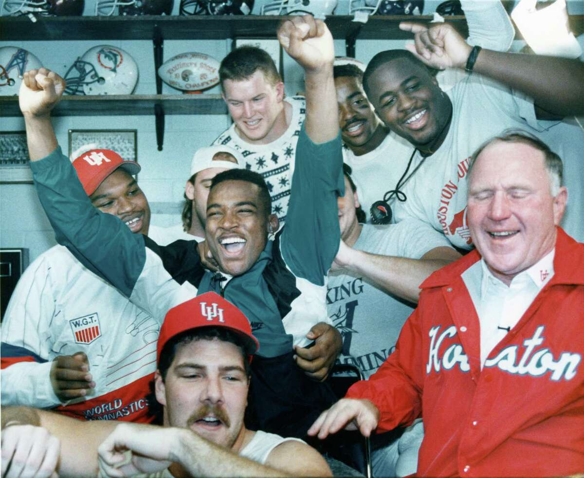 (HT6) HOUSTON, DEC 2, 1989 -- University of Houston quarterback Andre Ware with hands up Saturday as he was named the winner of the Heisman Trophy. At right is his coach Jack Pardee.