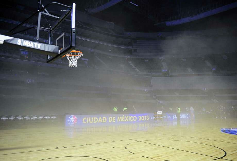 General view inside Mexico City Arena where players were evacuated because of smoke before the game between Minnesota Timberwolves and San Antonio Spurs in Mexico City on Dec. 4, 2013. A transformer burned and spread smoke on the court before the game. Photo: Alfredo Estrella /Getty Images / AFP