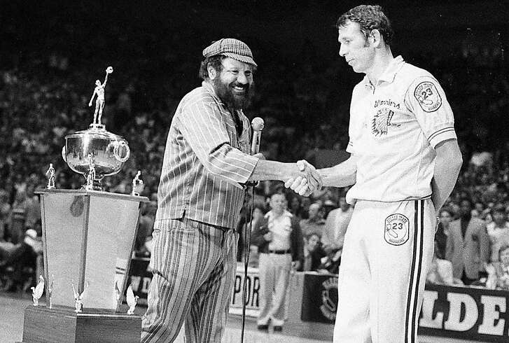 Warriors owner Franklin Mieuli shakes the hand of Jeff Mullins after the team's playoff victory over the Bullets at the Cow Palace near San Francisco. May 23, 1975.