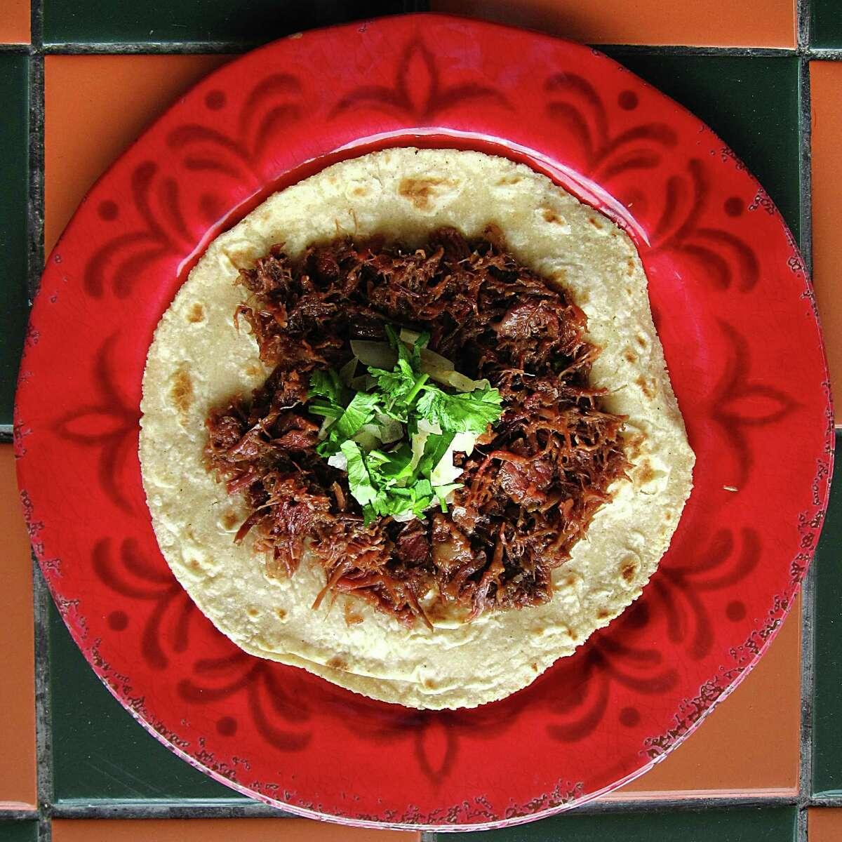 A barbacoa taco on a handmade corn tortilla from El Milagrito Cafe.