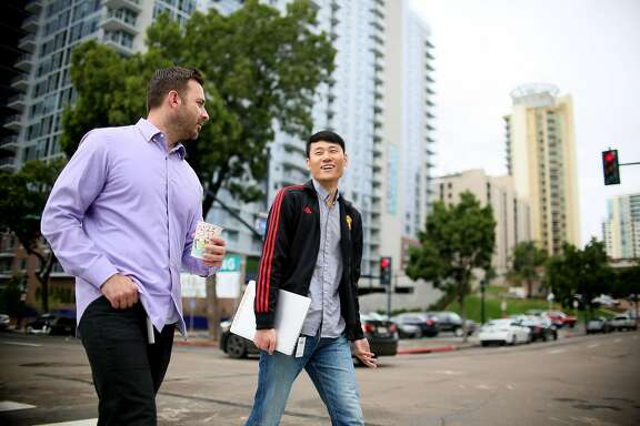 Kan Wang and engineer at Zeeto and an H-1B Visa holder, walks in Downtown San Diego with Brian Jones, near their offices on Friday, January 13, 2017.  The Trump administration says it plans on changing the nation's immigration process and will likely look at reforming the H-1B visa program. Many tech firms hire people through this program and some companies and entrepreneurs are concerned about whether changes could impact their hiring process.Photo by Sandy Huffaker/Special to The Chronicle)
