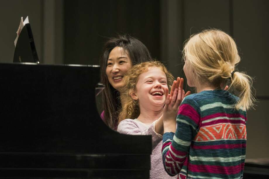 Midlanders Nina Swier, 10, laughs as she claps hands with her partner and friend, Madi Arthur, 10, at the end of a song while piano teacher MiJung Trepanier also laughs during a rehearsal for KeyboardFest on Friday at the Midland Center for the Arts. KeyboardFest, an annual piano festival sponsored by the Midland Music Teachers Association, will be Saturday at 7 p.m. The concert features 270 pianists playing duets on 13 grand pianos and is designed to teach ensemble skills to the musicians. Photo: Danielle McGrew Tenbusch/for The Daily News