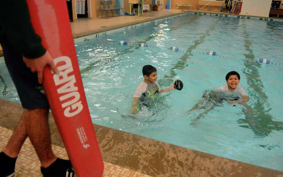 Lifeguard Niko Cruz, watches as Bryan Mota, 8, and Josiah Cruz, 9, right, play in the pool at the Cardinal Sheehan Center in Bridgeport, Conn., on Thursday Jan. 12, 2017. In light of the Bridgeport YMCA's decision to end adult memberships, the nonprofit center is considering opening its large pool to paying adults. Photo: Christian Abraham / Hearst Connecticut Media / Connecticut Post