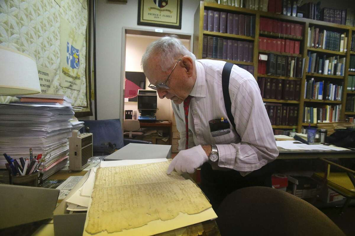 San Antonio archdiocese archivist Brother Edward Loch looks through a hand written book of records Thursday January 12, 2016 dating back to the 1700s at the archdiocese on West Woodlawn. Loch has been keeping records for the San Antonio archdiocese for about 30 years and is currently trying to digitize the Catholic records.