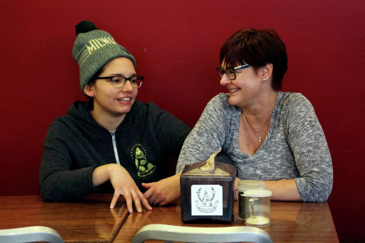 In this Jan. 9, 2017, photo, Andrea Ledesma, left, talks with her mother, Cheryl Romanowski, at Classic Slice pizza restaurant, where Ledesma works, in Milwaukee. Ledesma, 28, says her parents owned a house and were raising kids by her age. Not so for her, even though she has a college degree. With a median household income of $40,581, millennials earn 20 percent less than boomers did at the same stage of life, despite being better educated, according to a new analysis of Federal Reserve data by the advocacy group Young Invincibles. (AP Photo/Carrie Antlfinger) ORG XMIT: RPCA502