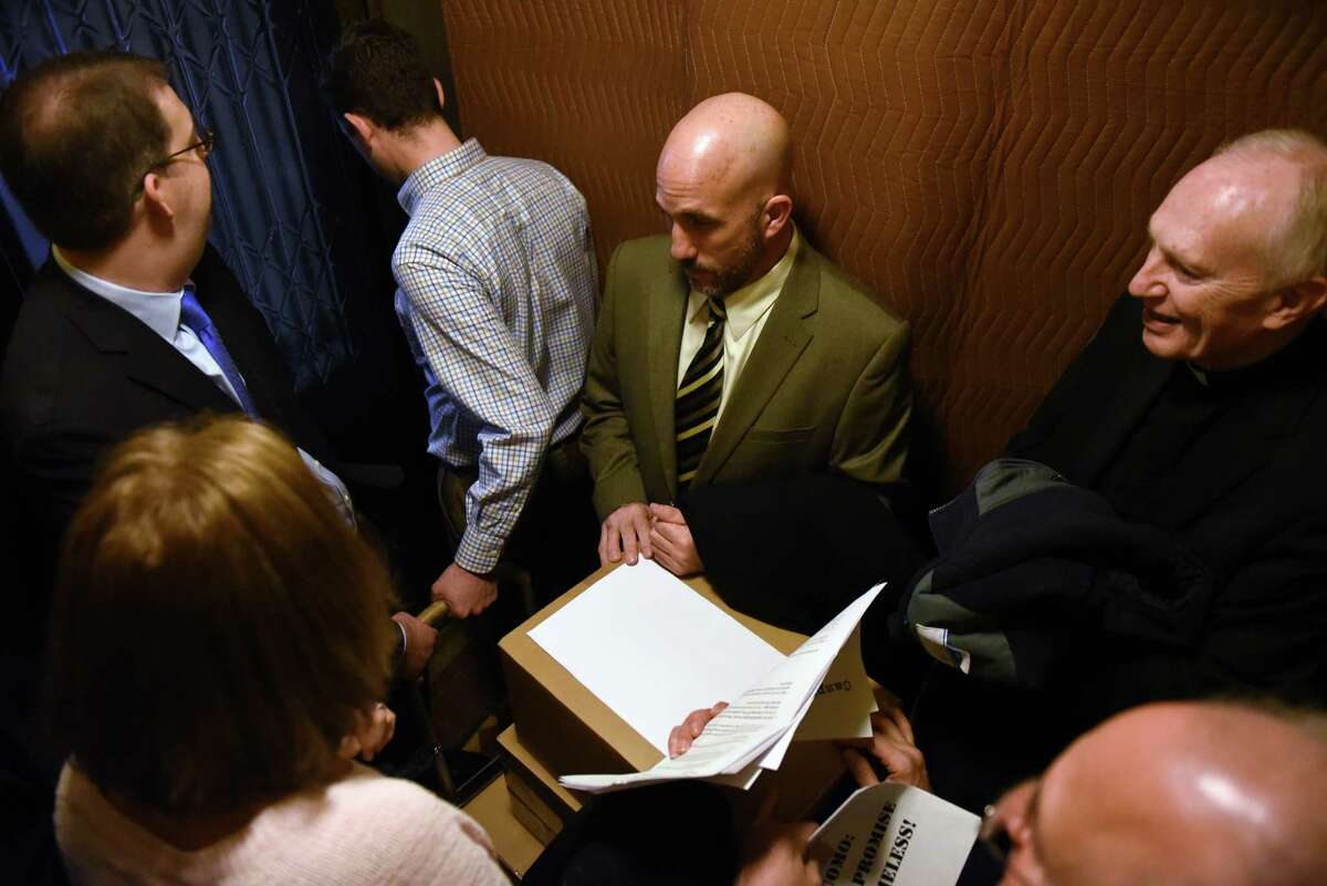 Michael Finocchi, executive director of Shelters of Saratoga, center, Bishop Emeritus Howard Hubbard, right, and other advocates for the homeless ride a Capitol elevator to the second floor with 25,000 letters they delivered to Gov. Cuomo?'s office on Friday, Jan. 13, 2017, in Albany, N.Y. The letters, from people across New York, demanded that the Governor keep his promise to fund thousands of units of supportive housing for the homeless in communities across the state. (Will Waldron/Times Union)