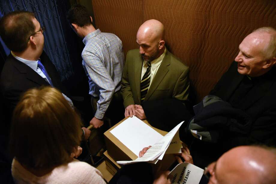 Michael Finocchi, executive director of Shelters of Saratoga, center, Bishop Emeritus Howard Hubbard, right, and other advocates for the homeless ride a Capitol elevator to the second floor with 25,000 letters they delivered to Gov. Cuomo's office on Friday, Jan. 13, 2017, in Albany, N.Y. The letters, from people across New York, demanded that the Governor keep his promise to fund thousands of units of supportive housing for the homeless in communities across the state. (Will Waldron/Times Union) Photo: Will Waldron / 20039438A