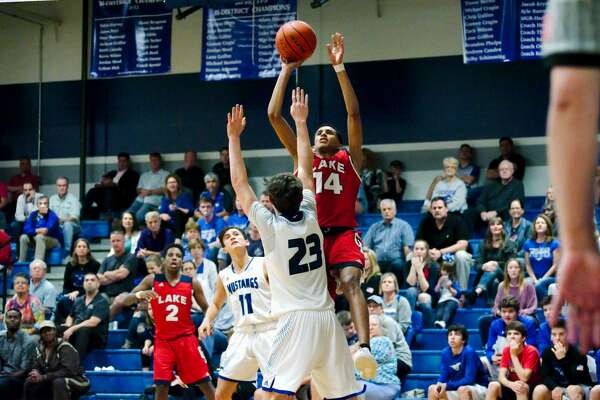 Clear Lake's Ajare Sanni (14) puts up a shot over Friendswood's Griffin Schneider (23) Friday, Jan. 13.