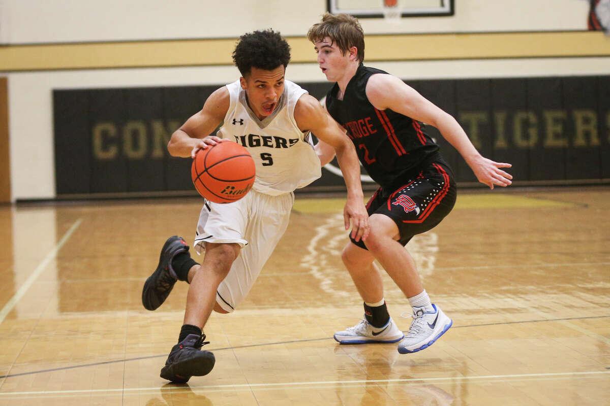 Conroe's Antonio Evans (5) drives downcourt as Oak Ridge's Tyler Dawson (2) defends during the varsity boys basketball game on Friday, Jan. 13, 2017, at Conroe High School. (Michael Minasi / Chronicle)