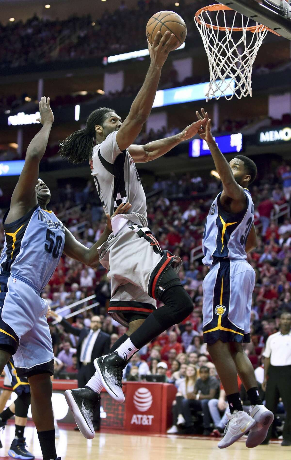 Houston Rockets center Nene Hilario, center, drives to the basket as Memphis Grizzlies forward Zach Randolph, left, and guard Troy Daniels defend in the second half of an NBA basketball game, Friday, Jan. 13, 2017, in Houston. Memphis won the game, 110-105. (AP Photo/Eric Christian Smith)