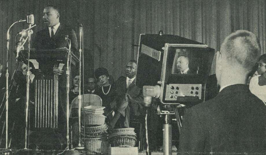 John E. Maher, then a sophomore at Darien High School, films the Rev. Martin Luther King Jr. speaking at Stamford High School on Nov. 30, 1964. Maher says King spoke so forcefully that when he shifted to the left and reached around to adjust the zoom lens in the front of the camera, he could feel King's breath on his hand. Photo: Contributed Photo / Stamford Advocate  contributed