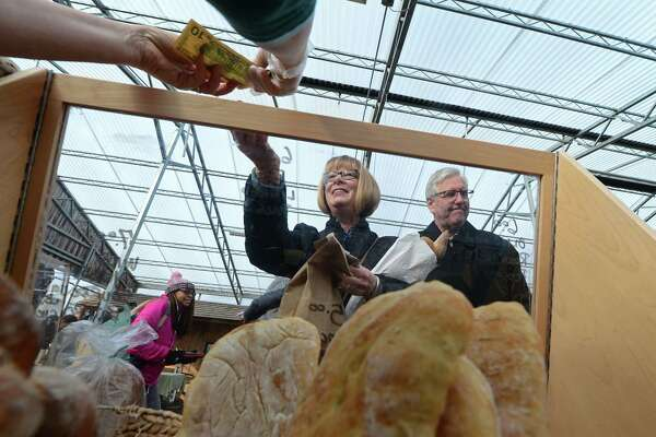 Leslie and Gary Orlowski purchase baked goods from Wave Hill Breads at the Westport Winter Farmers' Market at Gilbertie's Herb and Garden Center Saturday, January 14, 2017, in Westport, Conn. The Farmer's Market runs Saturdays through mid-March and will feature a cooking competition January 28 that will be judged by chefs from local restauramts.