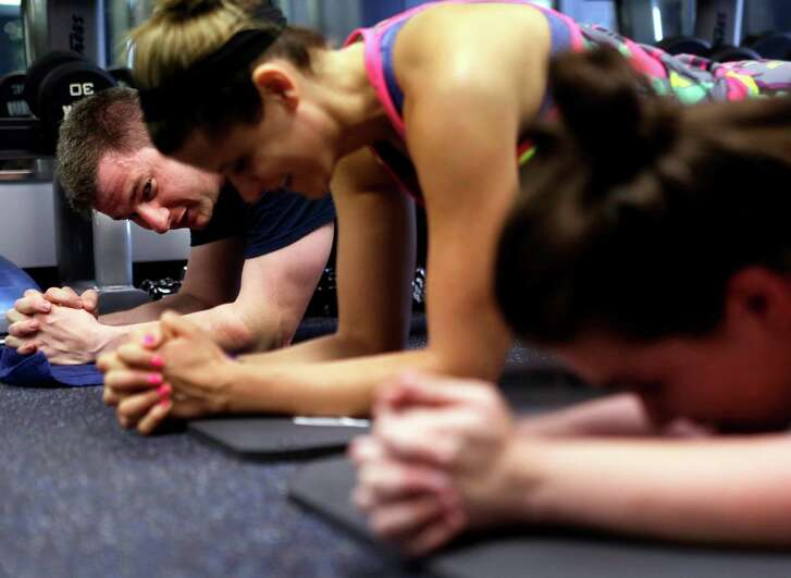 My House Fitness owner Chris Markos competes in a planking tiebreaker with his team during class on Saturday, July 16, 2016, in Houston. (Annie Mulligan / Freelance)